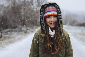Girl smiling on a snowy winter day.