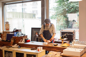 Bearded Male Hipster Shop Assistant Wrapping Gift on Shop Counter