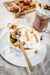 Recipes with pumpkins, fast food, microwave meal. Spicy pumpkin pie in mug, with whipped cream, ice cream, cinnamon, anise. On white wooden table, with cup of hot chocolate. Copy space