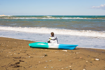 Young caucasian man sitting on beach with kayak, back view