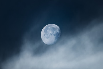 Moon with light clouds in its waning gibbous phase during morning