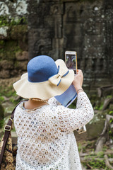Asian woman wearing a hat taking pictures of temples of angkor with her mobile phone.