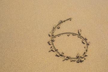 Six number written on sand on summer beach