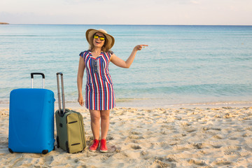 Happy laughing woman tourist with suitcases standing near the sea and pointing on copy space. Travel and summer vacation concepts