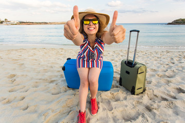Beach, Holiday, Vacation and Happiness Concept - young smiling woman near the sea with her luggage showing thumbs up gesture