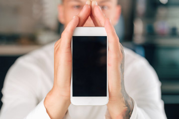 Man is holding white smartphone. Smart home concept.