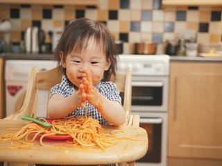 baby girl eating messy spaghetti at home