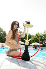 attractive girl with a hookah in the pool with blue water background