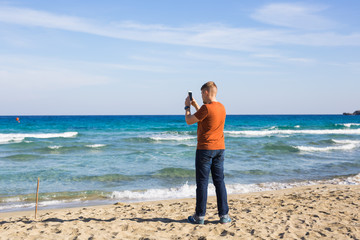 man taking photos of sea with mobile phone.