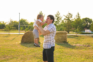 Happy young father and son playing together and having fun in the summer or autumn field. Family, child, fatherhood and nature concept