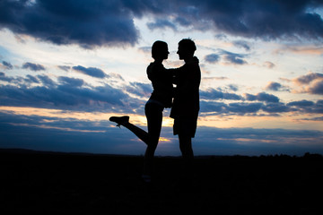 Silhouette lovely couple in a field at sunset with a dramatic sky on a background