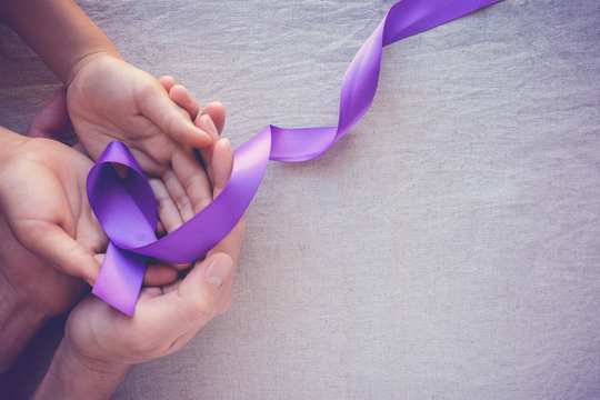 Hands holding Purple ribbons, world cancer day background, Alzheimer disease, Pancreatic cancer, Epilepsy awareness, domestic violence awareness
