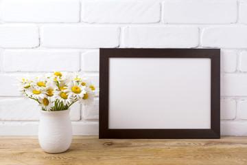 Black brown  landscape frame mockup with chamomile bouquet in rustic vase
