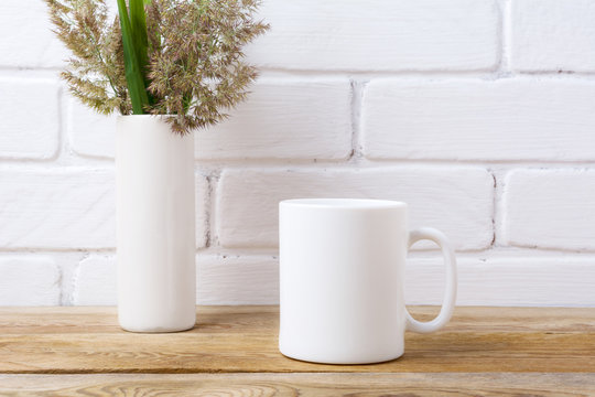 White coffee mug mockup with grass and green leaves in cylinder vase