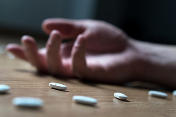Drug addiction, medical abuse and narcotics hook and dependence concept. Drug addict with withdrawal symptoms lying on floor. Tablet overdose. Suicide and death. Hand surrounded by many pills.
