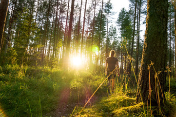 Young woman walking in forest path at sunset. Summer night in nature at dawn. Carefree lifestyle....