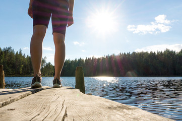 Young woman standing on an old wooden dock and pier at a lake at summer in Finland. Sun shining in blue sky. Traditional Finnish nature view.