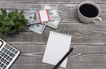 Notepad, fountain pen, packs of American dollars, a cup of coffee, a plant, a calculator against the background of a wooden table.