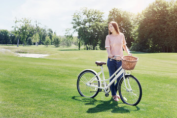 Cheerful woman with vintage bicycle on lawn on sunny day