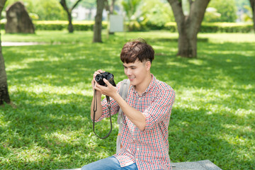Young smiling man taking picture in the park