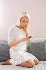 Portrait of happy young woman with mobile phone sitting on couch at home
