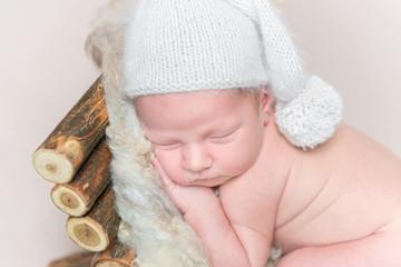 Newborn baby sleeps on a wooden crib