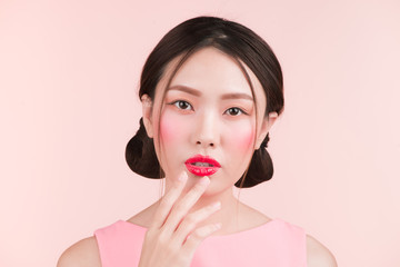 Portrait of beautiful woman with bright makeup and red lips over pink background.