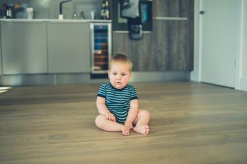 Little baby sitting on the floor in kitchen