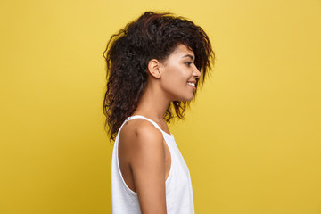 Side view portrait of beautiful attractive African American woman over yellow studio background. Copy Space.