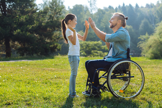 Young father with mobility impairment high-fiving daughter