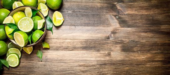 Ripe limes in a bowl. Wall mural