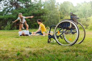 Disabled man lifting up his daughter on picnic