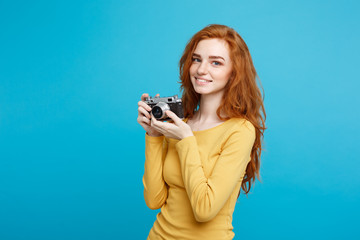 Close up Portrait young beautiful attractive ginger girl happy smiling with vintage camera and ready to travel. Blue Pastel Background. Copy space.
