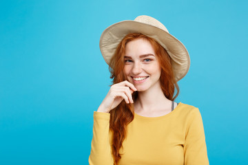 Travel concept - Close up Portrait young beautiful attractive redhair girl with trendy hat and smiling. Blue Pastel Background. Copy space.