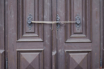 Old church door secured with string.