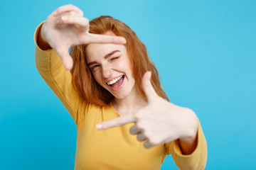 Portrait of young beautiful ginger woman with freckles cheerfuly smiling making a camera frame with fingers. Isolated on white background. Copy space.