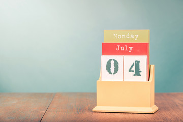 4th of July on retro wooden desk calendar. USA Independence Day date. Vintage instagram style filtered photo