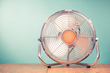 Retro portable office or home cooling fan in working mode standing on table. Vintage instagram style filtered photo