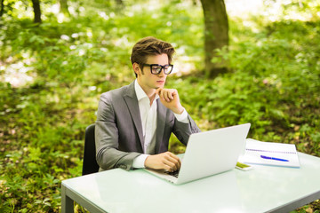 Side view of Young handsome business man working at laptop at office table in green park. Business concept.