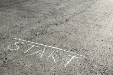 "The inscription of crayons ""Start"" on the asphalt. The concept of the beginning of something"