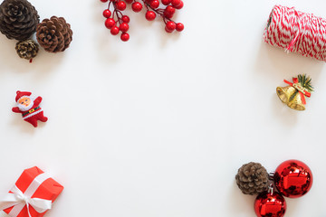 Christmas and New Year background. Frame made of christmas decoration with pine cones, holly berry, christmas balls, rope roll, gift. Creative flat lay, top view design.