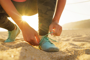 Running shoes - woman tying shoe laces on sandy beach at sunset