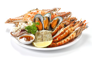 Roasted Mixed Seafood Contain Blue Crabs, Mussels, Big Shrimps, Calamari Squids and Grilled Barracuda Fish Garlic with Spicy Chili Sauce and Lemon on Dish, Isolated on White Background with Shadow.