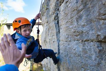 Boy climber gives five.