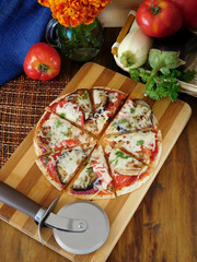 Vegetable pizza cut into segments on a wooden board surrounded by vegetables