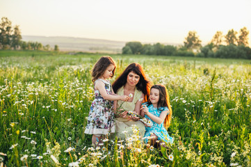 Mom with baby in daisy field at sunset. Toning