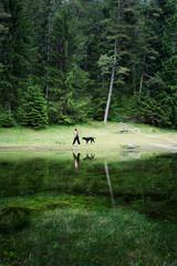 woman with dog walking along lake