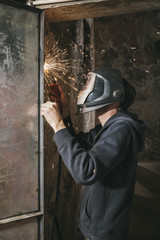 Welder wearing protection mask welding a metal door