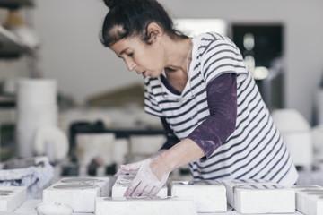 Female ceramic artist arranging moulds in her studio