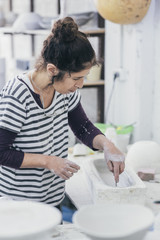 Female ceramic artist working on a mould